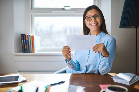Smiling woman in glasses holding envelope