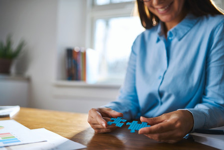 Selective focus of happy worker with puzzle pieces
