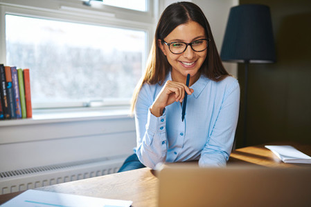 Smiling young businesswoman working at home