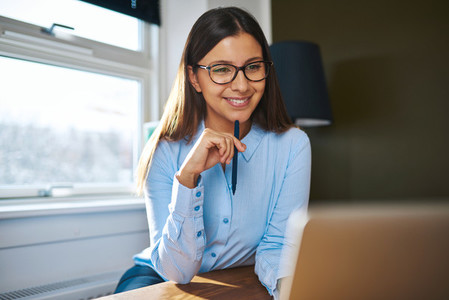 Positive self employed woman working near window