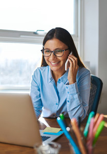 Smiling woman on phone behind laptop
