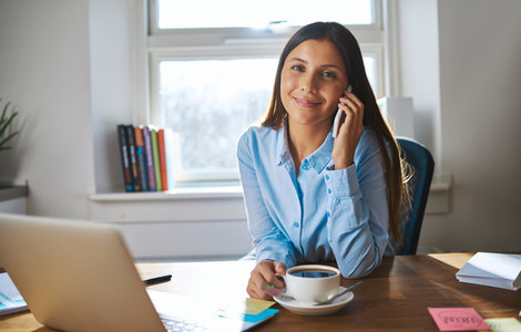 Smiling female on phone with coffee and computer