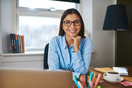 Smiling female entrepreneur at her desk