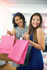Two happy young ladies out shopping