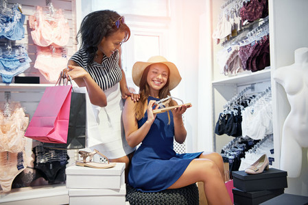 Trendy young women choosing a pair of shoes