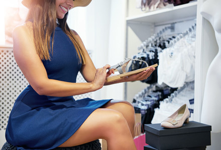 Smiling young woman looking at a pair of sandals