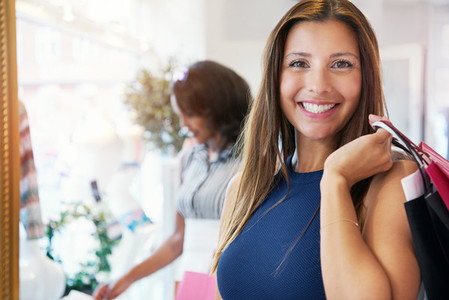 Attractive happy young woman shopping for clothes
