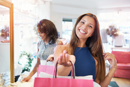 Vivacious young woman shopper grinning at camera