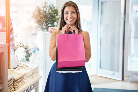 Cute young woman posing with her shopping bags