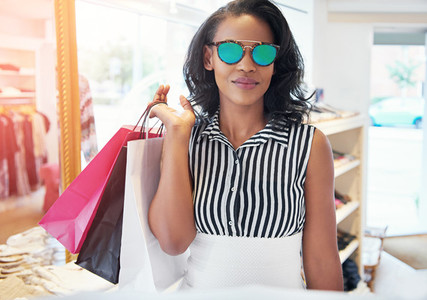 Trendy young woman shopping in sunglasses