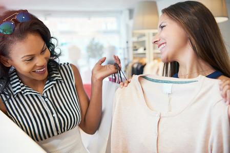 Happy young female friends choosing a garment