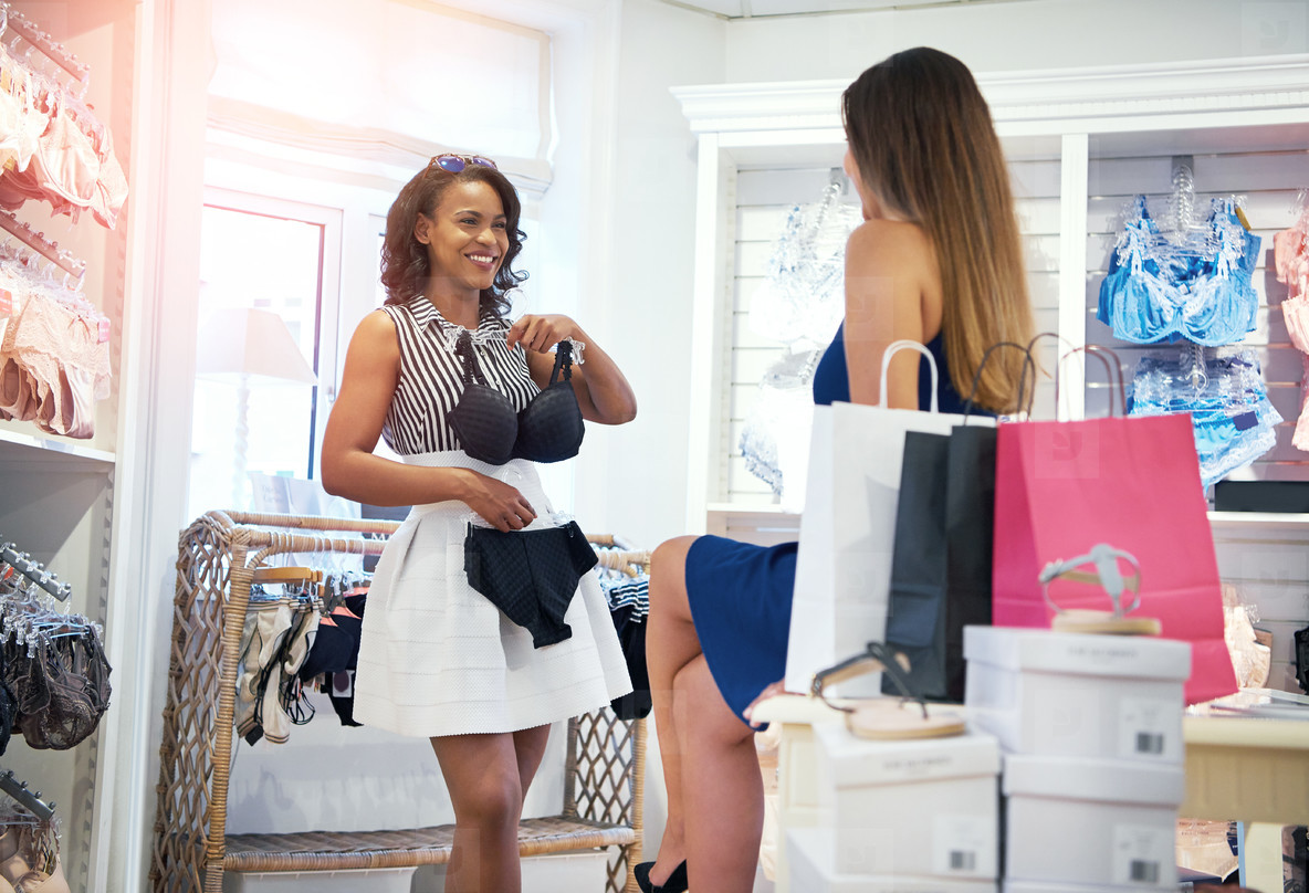 Two happy chic young woman shopping for lingerie