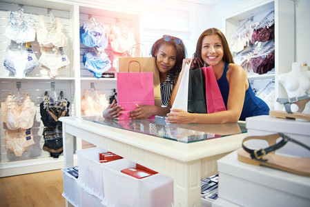 Two happy women friends shopping for lingerie