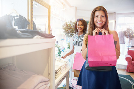 Happy woman shopping with friend at store