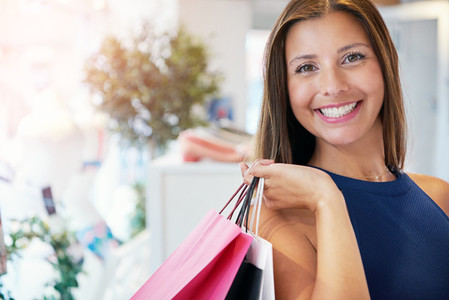 Happy woman holding assorted shopping bags