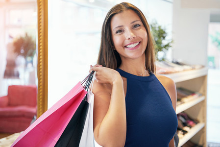 Smiling shopper holding assorted shopping bags