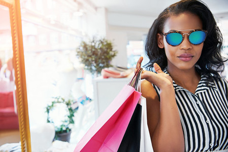 Female shopper holding bags with calm expression
