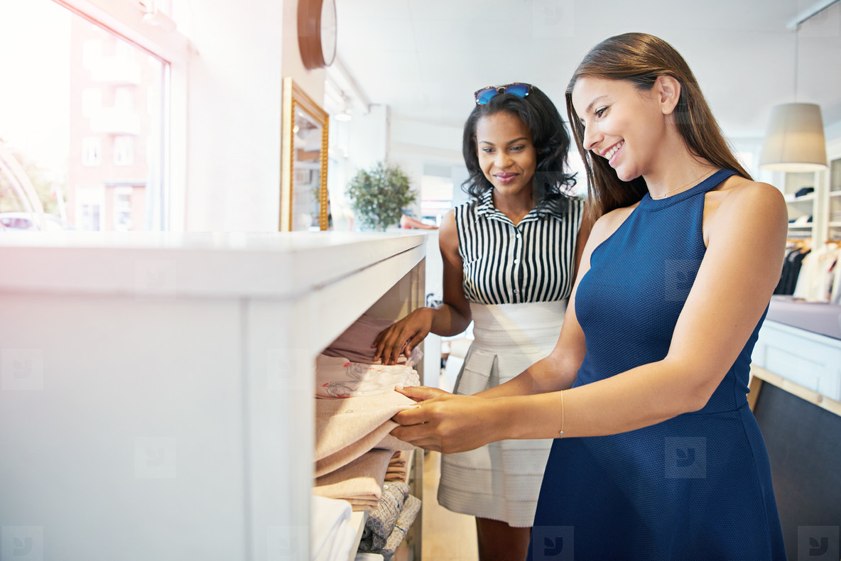 Female friends picking up various clothes in store
