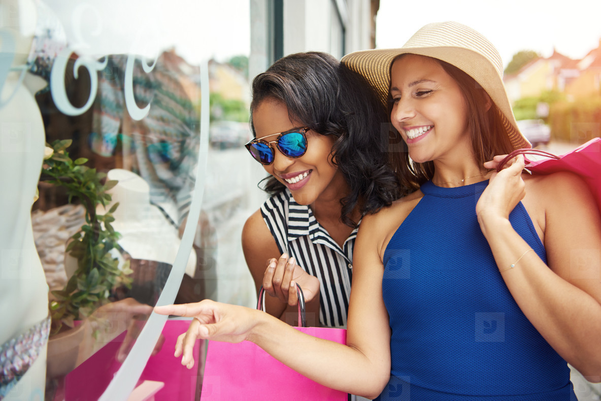 Gorgeous friends looking at clothing in window