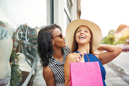 Multiracial friends window shopping together