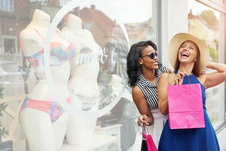 Laughing friends next to bikini display