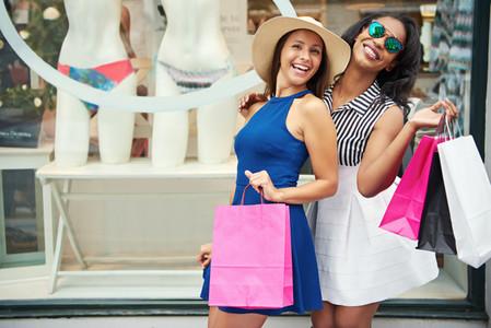 Friends posing in front of bikini store window