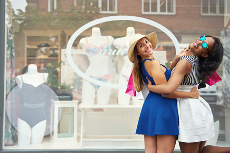 Cute friends embracing in front of window