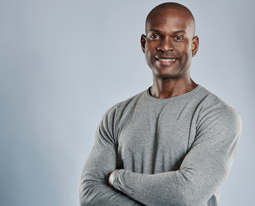 Cheerful black man with folded arms in gray
