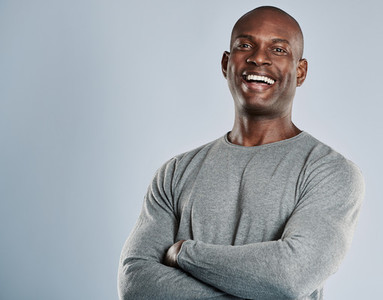 Laughing African man in gray shirt with copy space