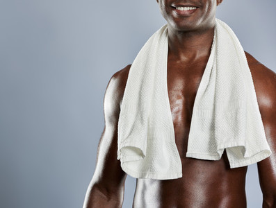 Towel over shoulders of muscular smiling man
