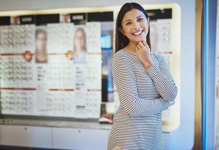 Beautiful happy woman in eye wear store