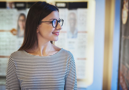 Young woman looking sideways in new eyeglasses