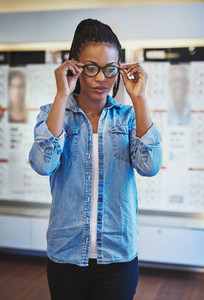 Cute young woman trying on new eyeglasses