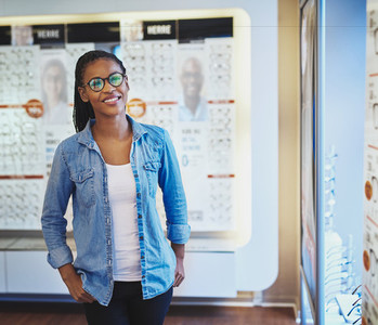 Smiling female in front of eyeglasses display