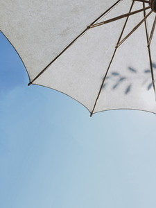 White umbrella on sunny blue sky