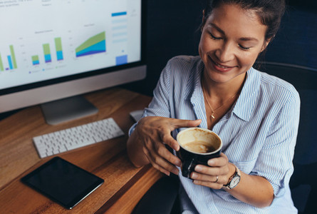Businesswoman having coffee break in office