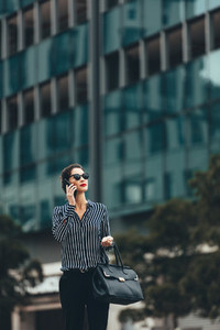 Asian woman walking on the street with mobile phone