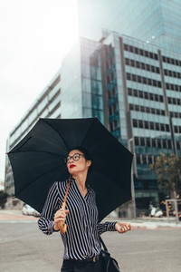 Asian businesswoman on city street with umbrella