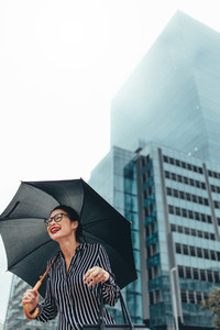 Businesswoman outdoors in the city with umbrella