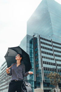 Young businesswoman on city street with umbrella