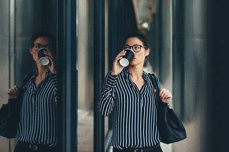 Woman outside business center drinking coffee