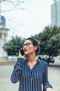 Asian businesswoman walking outside using mobile phone