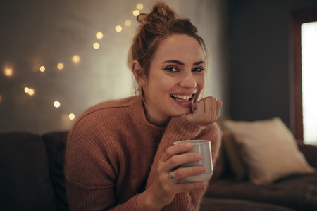 Smiling woman sitting at home with a cup of coffee