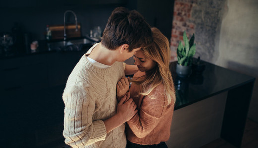 Romantic young couple embracing in the kitchen at home