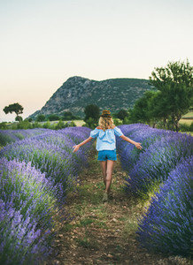Young blond woman traveller walking in lavender field Isparta Turkey