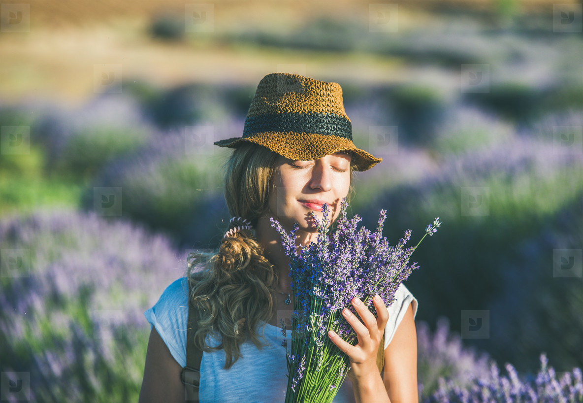 Young girl wearing straw hat with bouquet of lavender flowers