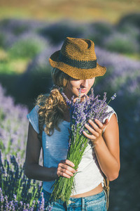 Girl wearing straw hat with bouquet of lavender flowers