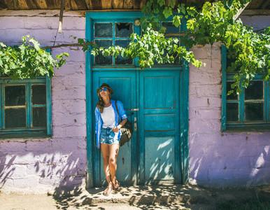 Girl in hat standing near purple wall in Turkish village