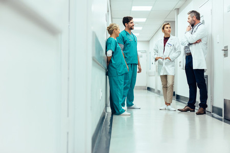 Team of doctors having discussion in hospital corridor
