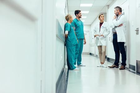 Team of doctors having discussion in hospital corridor